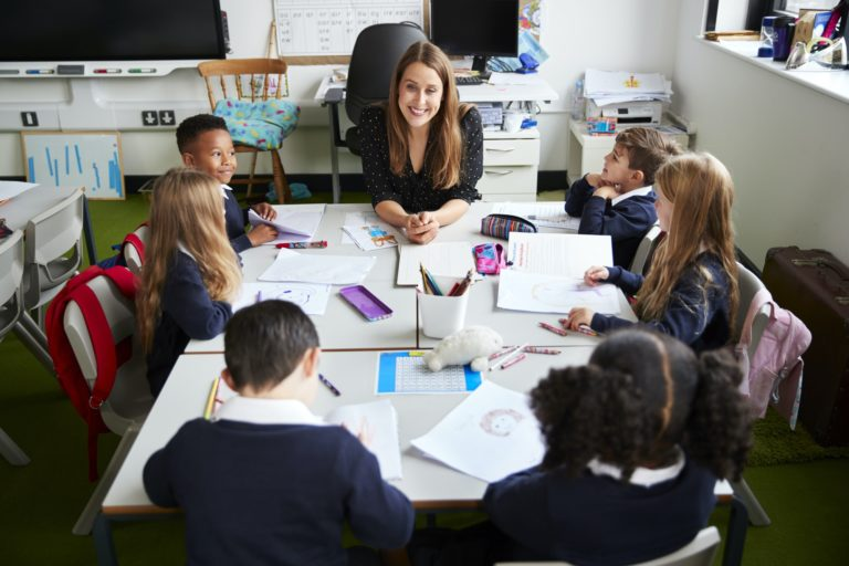 Elevated view of female primary school teacher in a classroom with schoolchildren