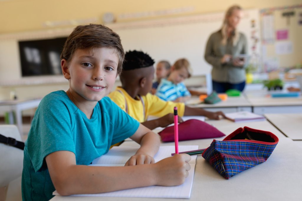 Schoolboy sitting at a desk in an elementary school classroom