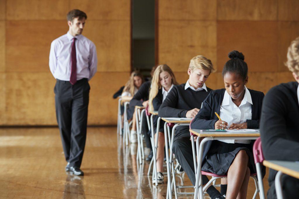 Teenage Students Sitting Examination With Teacher Invigilating