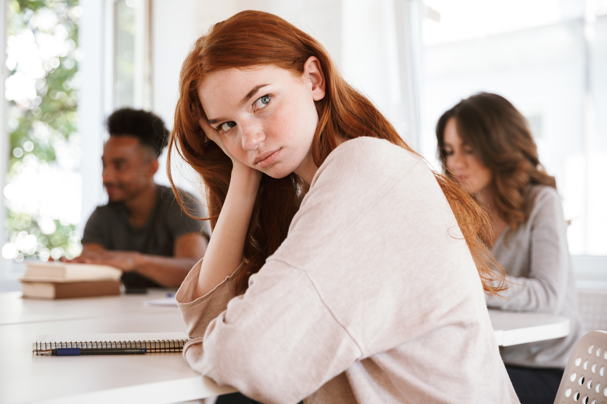Tired young redhead lady looking aside